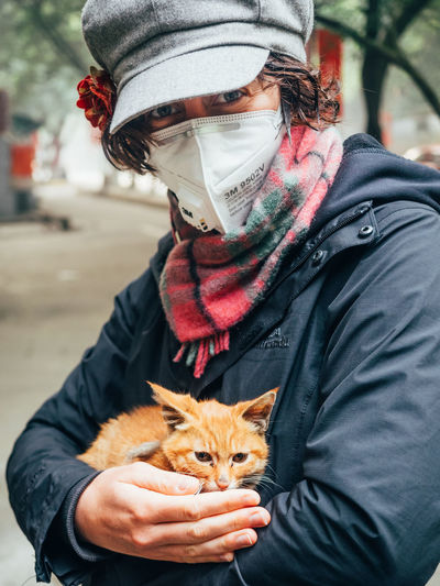 Animal Themes Cat China Day Dog Domestic Animals Knit Hat Lifestyles Mammal One Animal One Person Outdoors People Pets Real People Warm Clothing