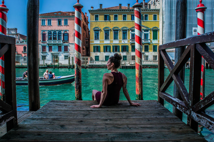 Rear view of woman sitting on pier over canal