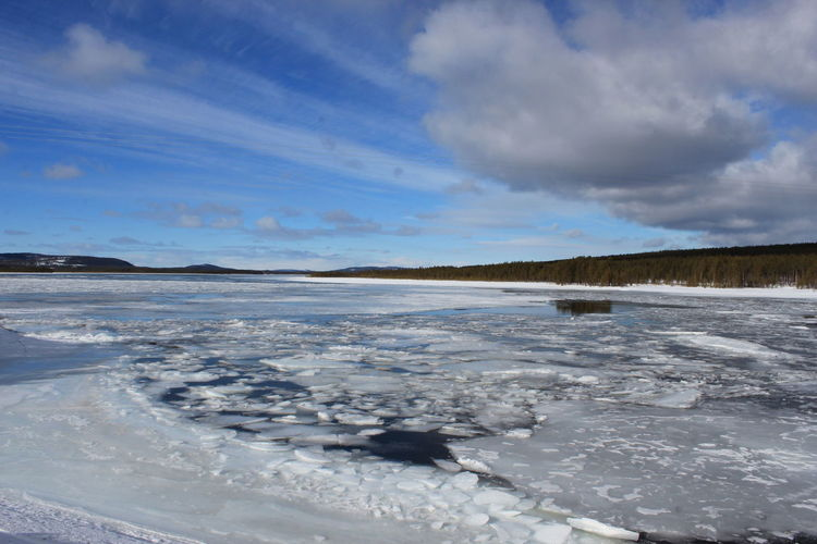 Frozen lake against cloudy sky