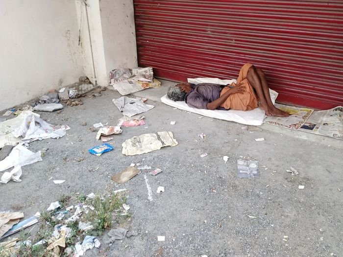 High angle view of poor man sleeping outdoors