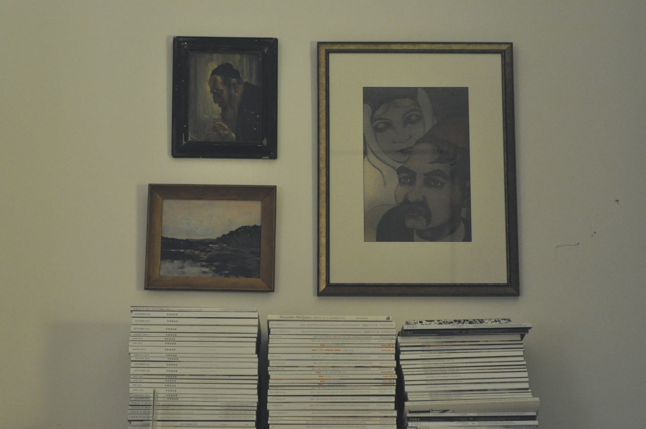 Stacked Magazines By Picture Frames On Wall