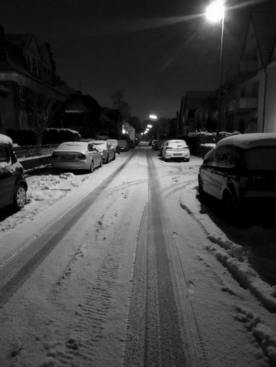 Cars on road in city at night during winter