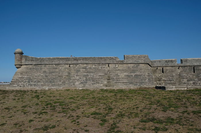 Side view of Castillo de San Marcos in St Augustine, Florida, USA. Oldest fortress in America built in 1672 in Matanzas Bay Florida. Blue skies no clouds. Historic landmark. Castillo De San Marcos Fort Fortress Historic Architecture Historical Building Historical Monuments St Augustine St Augustine Florida St Augustine, FL