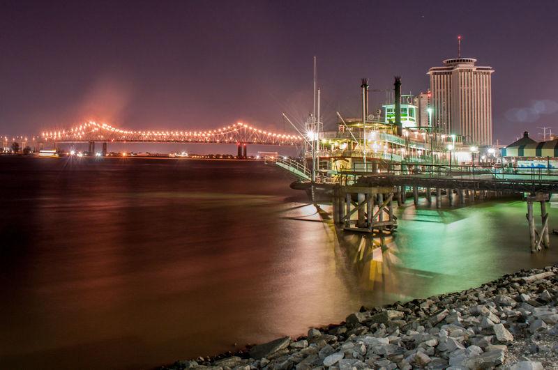 Illuminated bridge over sea at night