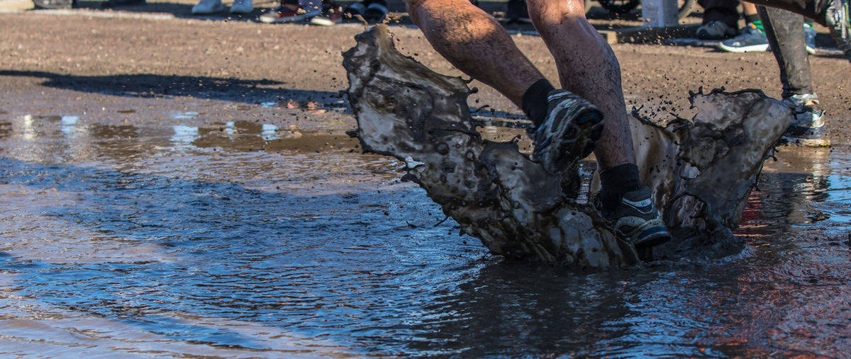 Low section of men running in muddy water