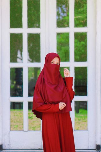 Woman in hijab standing against window
