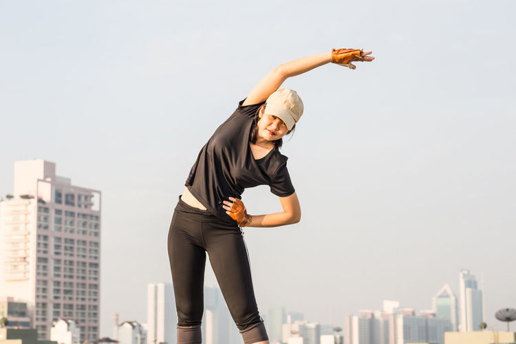 Woman Exercising Against Sky