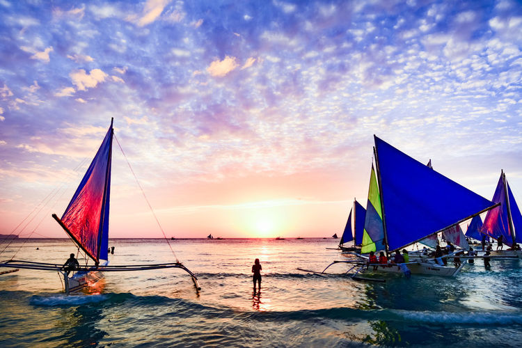 Tourists on boat at island of boracay during sunset