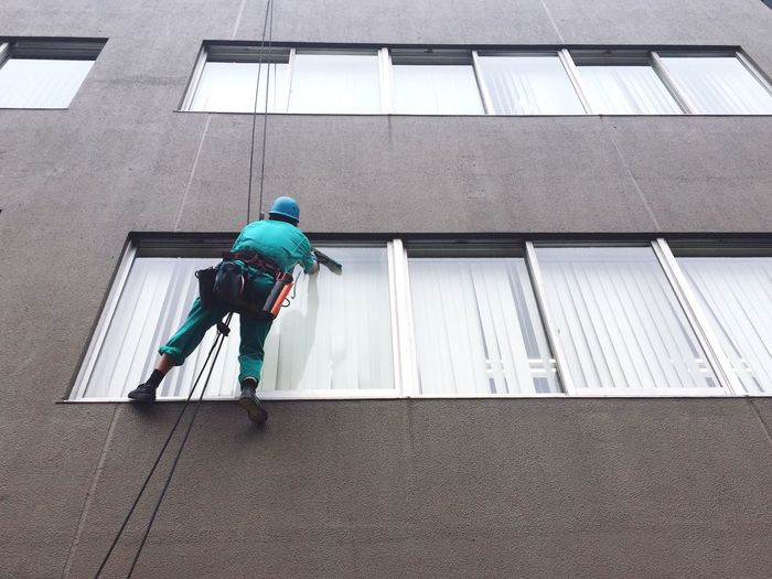 Low angle view of man cleaning window