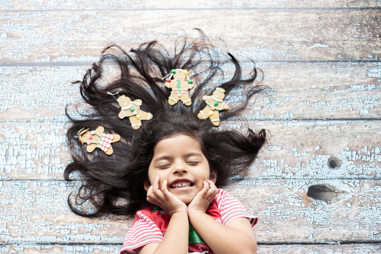 Cute cheerful smiling girl with decorated Christmas hair Childhood Child Portrait One Person Looking At Camera Smiling Happiness Emotion Lying Down Headshot Front View Offspring Fun Toothy Smile Innocence Flower Teeth Black Hair Cute Outdoors Hairstyle