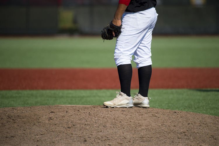 close up of baseball players legs with black stockings standing on first base Baseball Active Athlete Ball Body Part Clothing Competition Competitive Sport Day Focus On Foreground Gloves Human Body Part Human Leg Leisure Activity Lifestyles Low Section One Person Playing Field Real People Sport Sports Clothing Springtime Standing