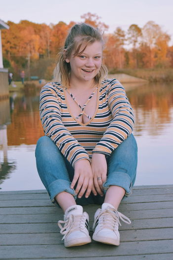 Portrait of smiling young woman sitting on lake against trees