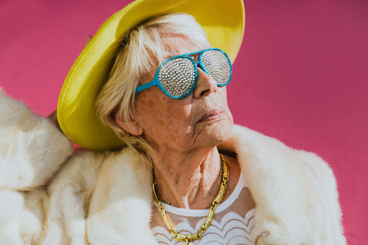 Close-up of senior woman wearing hat and sunglasses against pink background