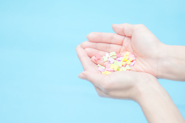 Human hands holding candies