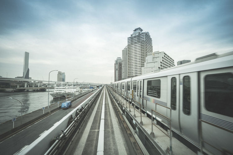 Transportation Architecture Mode Of Transportation City Built Structure Sky Building Exterior Rail Transportation Public Transportation Train Office Building Exterior Motion Train - Vehicle Skyscraper Travel No People Track Building Day Railroad Track Outdoors Subway Train Modern