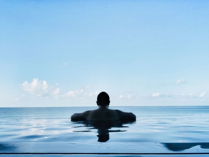 Rear view of shirtless man swimming in infinity pool against sea