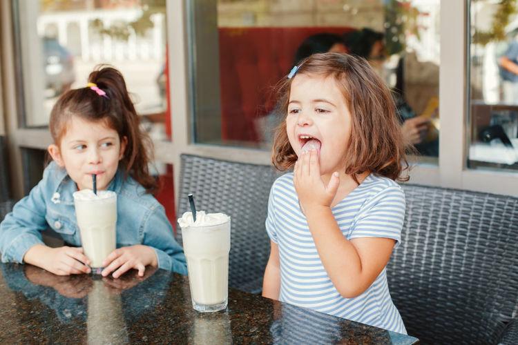 Siblings having milk shake at table in restaurant