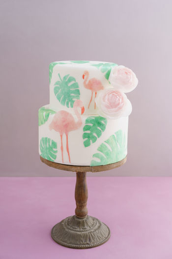 Two tiered tropical wedding cake with fondant, tropical wafer paper leaves and flamingos with ranunculus flowers on wooden cake stand Flamingo Cake Cake Stand Cakestand Tropical Tropical Wedding Cake Wafer Paper Waferpaper Wedding Cake