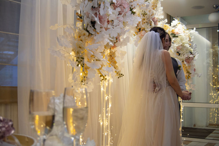 Celebration Wedding Bride Wedding Dress Flower Newlywed Indoors  Women Belief Adult Standing Happiness Young Adult Married Bouquet Flower Arrangement Wedding Ceremony Positive Emotion Event Life Events Champagne Champagne Glasses Focus On Background Togetherness Lifestyle