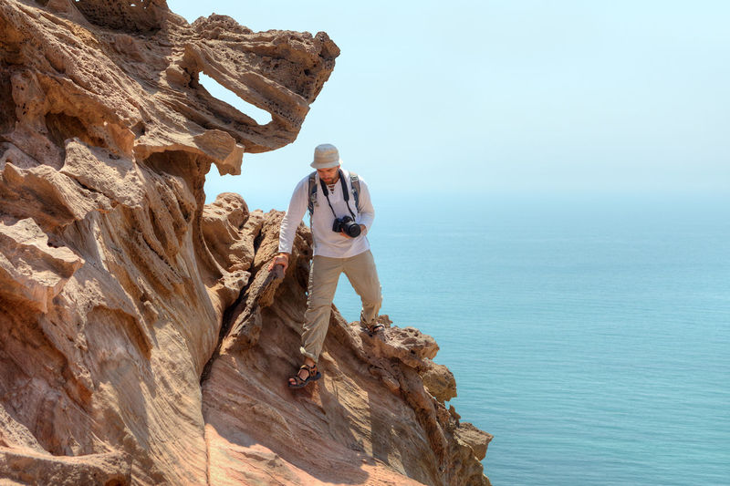Man on rock formation against sky