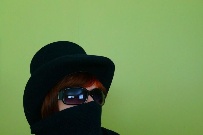 Close-Up Of Woman Wearing Hat And Sunglasses Against Green Background