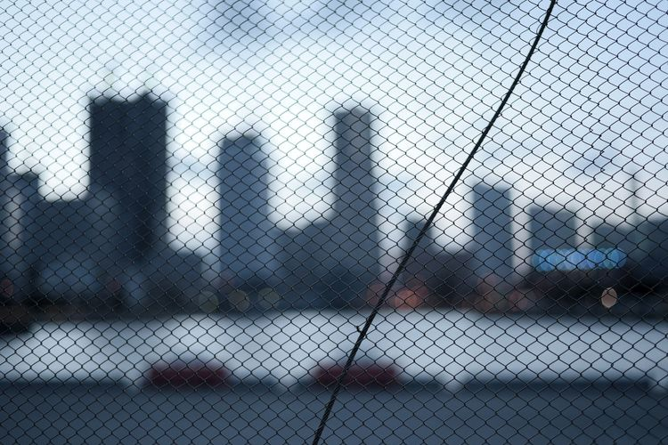 Close-up of chainlink fence against cloudy sky