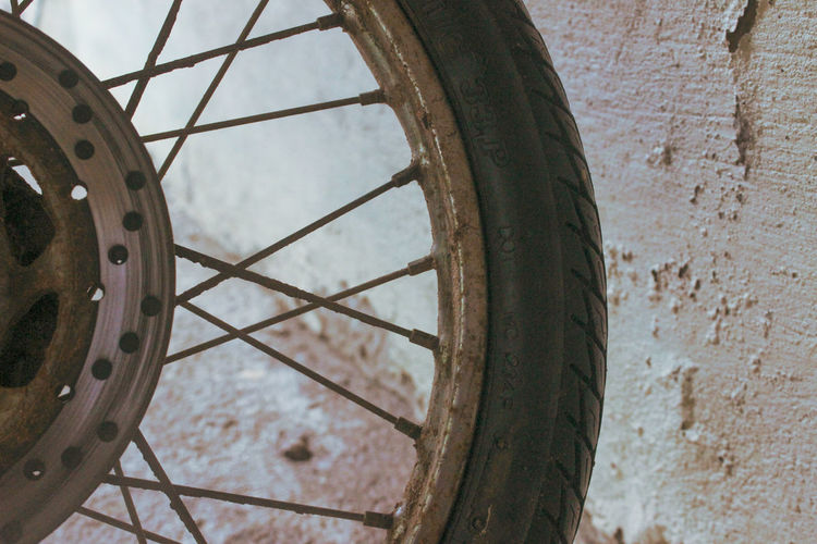 Close-up of bicycle wheel against wall