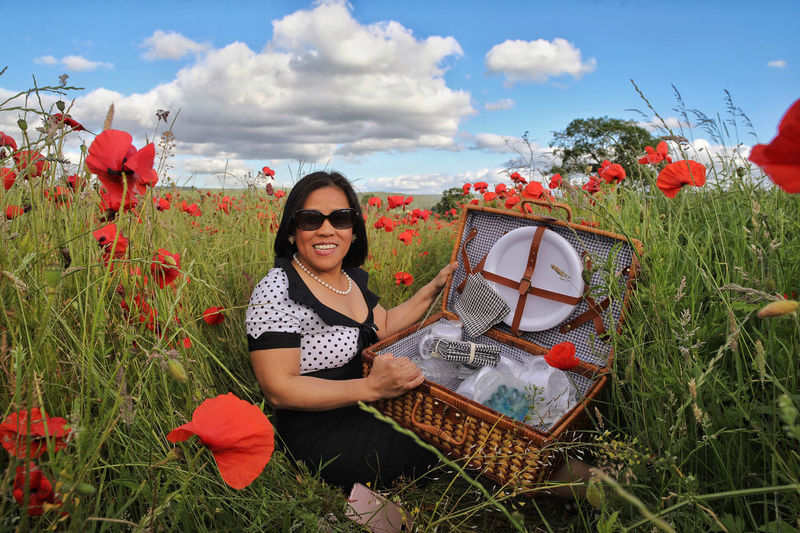 Portrait of happy woman holding picnic basket while sitting amidst red poppy flowers
