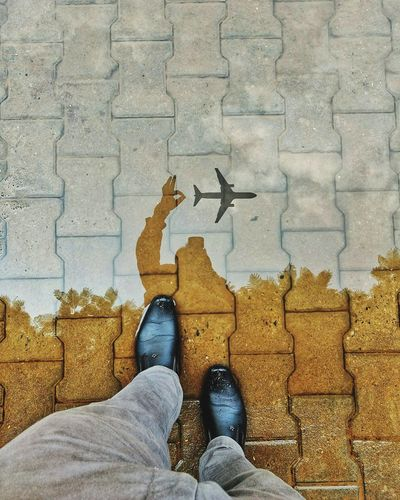 Low section of man standing by airplane reflection on footpath