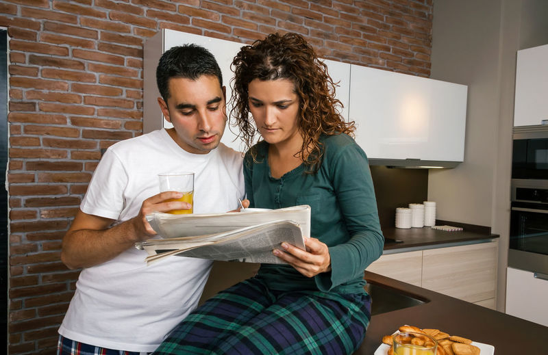 Couple having breakfast in the kitchen and reading the newspaper Horizontal Modern Brick Wall Croissant Surprised Serious Portrait Biscuits Sharing  Morning Together Orange Juice  Coffee Indoor Real Two Incredulous Young Woman Curly Hair Journal Wife Reading Standing People Concerned Married Man Male Lifestyle Husband Talking Caucasian Home Girl Female Entertainment Watching Interested Kitchen Bad News Newspaper Looking Breakfast Pajama Couple Worried