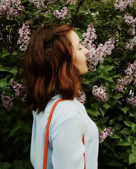 Side view of a young woman standing against plants