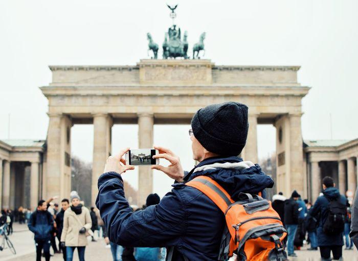 Man photographing brandenburg gate