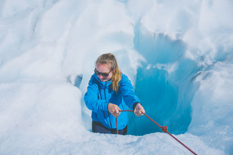 High Angle View Of Young Woman Pulling Rope While Standing Amidst Snow