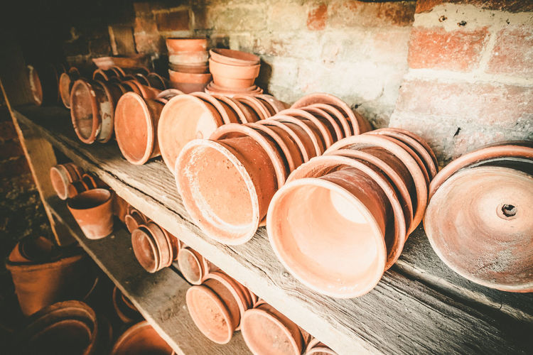Terracotta plant pots in a gardening shed. Abundance Art And Craft Brown Business Ceramics Choice Clay Close-up Container Craft Crockery Earthenware Gardening Equipment Gardening Pots Indoors  Large Group Of Objects No People Plant Pots Pottery Stack Still Life Terracotta Pot Terracotta Pots Variation Wood - Material