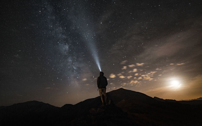 Rear view of man flashing light while standing on mountain against sky