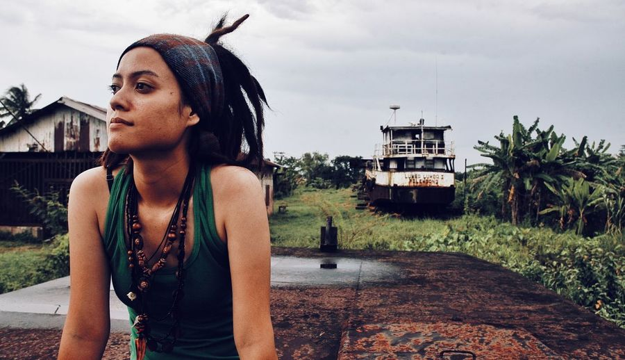 Young dreadlock woman looking away while standing against sky