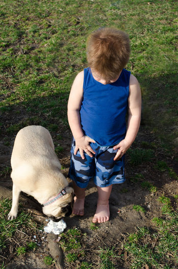 a little boy stares in horror as a pug dog eats his fallen ice cream Pug Animal Animal Themes Boys Casual Clothing Child Childhood Day Dog Domestic Animals Dropped Ice Cream Friendship Full Length Grass Leisure Activity Mammal One Animal One Person Outdoors People Pets Puppy Real People