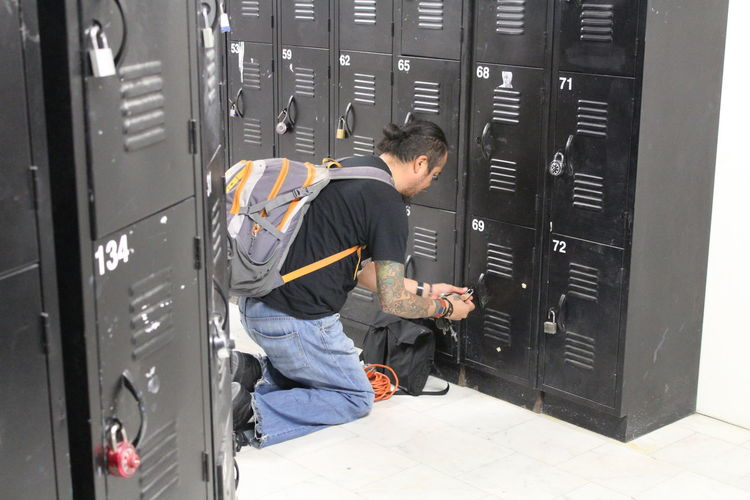 Side View Of Backpacker Opening Locker