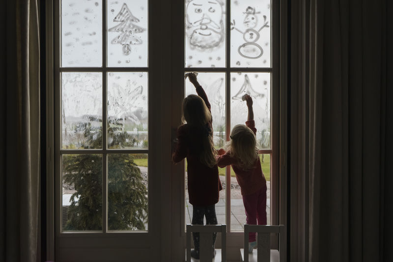 Children cleaning by window after christmas holidays.