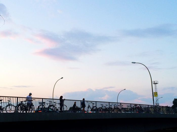 Railing against cloudy sky at sunset