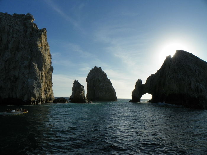 Arch of cabo san lucas and rock formation in sea against sky
