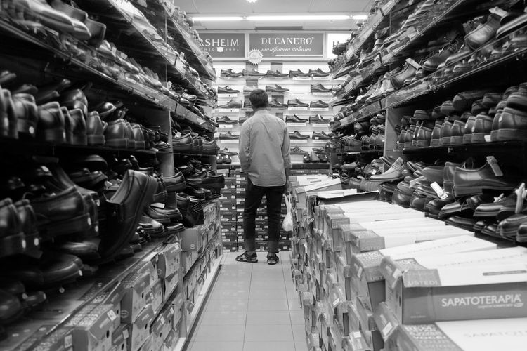 Rear View Retail  Store One Person Supermarket Business Finance And Industry Standing Indoors  One Man Only Full Length Men Adult Large Group Of Objects The Way Forward Groceries People Shelf Grayscale Monochrome NocolorStreet Photography Urban Exploration Urban Light And Shadow Black And White