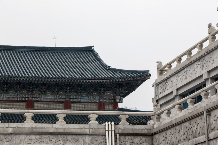 Architectural Feature Architecture Building Building Exterior Built Structure City Clear Sky Copy Space Day Exterior Famous Place Fence Gyungbok Palace High Section Historic Place History Korean Traditional Architecture Low Angle View Museum No People Outdoors Roof Sky Tourism Travel Destinations