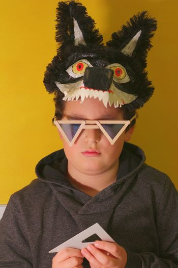 Portrait of boy holding carnival mask against yellow background