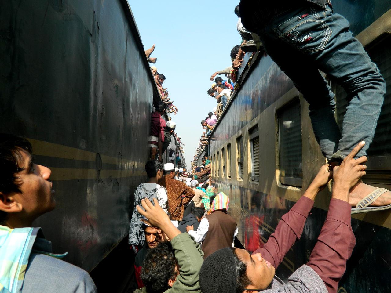 Crowd on train against sky