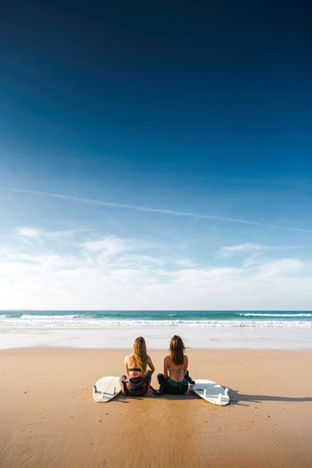 Rear view of female friends sitting at beach against blue sky