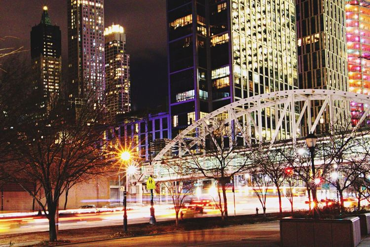 Long exposure in the city Illuminated City Night Architecture Lighting Equipment Building Exterior Street Built Structure Street Light Road Tree Skyscraper Outdoors City Life Cityscape Sky Canonphotography Throughmyeyes Traveling City At Night Low Shutter Speed