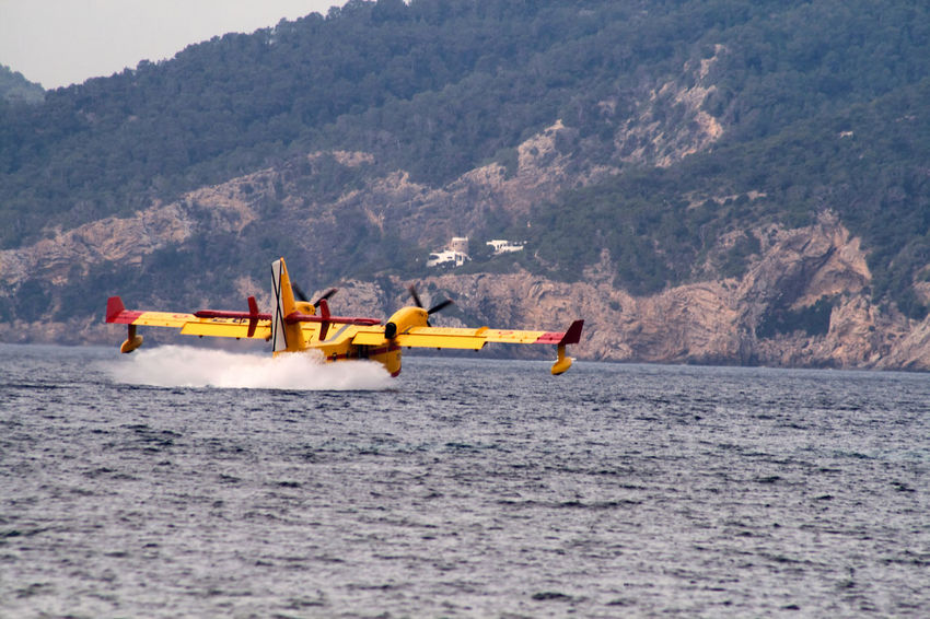 Adventure Beauty In Nature Blue Canadair Day Firefighter FireFighting  Flying Kayak Landscape Mode Of Transport Mountain Nature Nautical Vessel Oar Outdoors People Recreational Pursuit Red Sea Sky Transportation Vacations Water Yellow