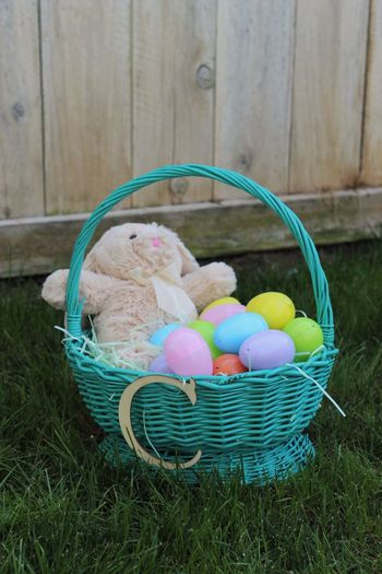 Close-up of easter eggs and bunny in wicker basket at yard