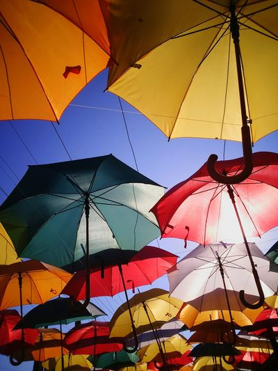 Low Angle View Of Colorful Umbrellas Hanging By Ropes Against Sky In Dalyan